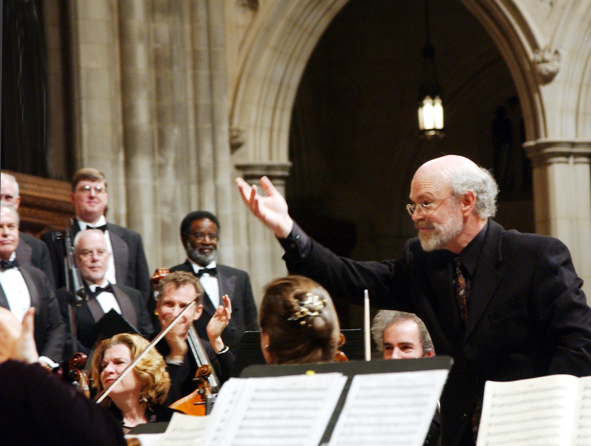 A conductor gestures his hand for an orchestra to stand for applause
