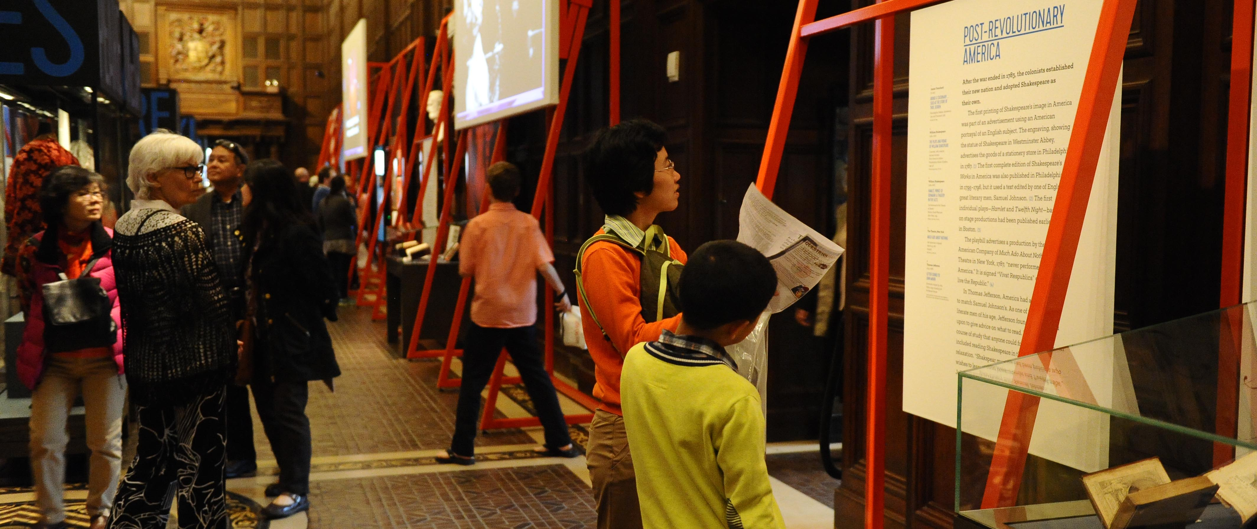 Visitors looking at an exhibition in the Folger Great Hall in 2016