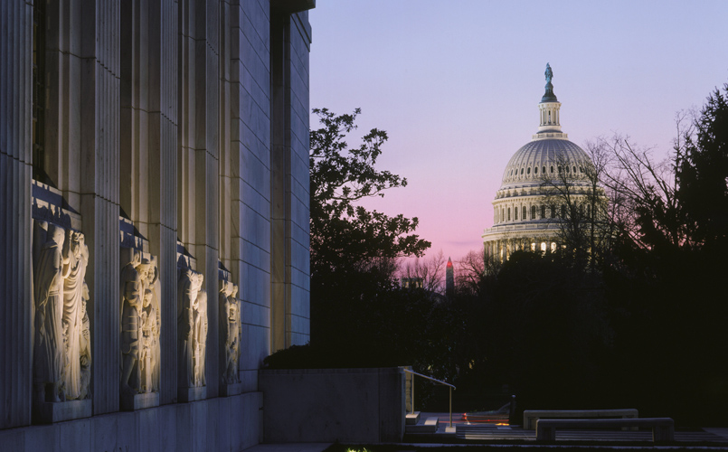 An evening view of the Folger Shakespeare Library with the US Capitol in the background