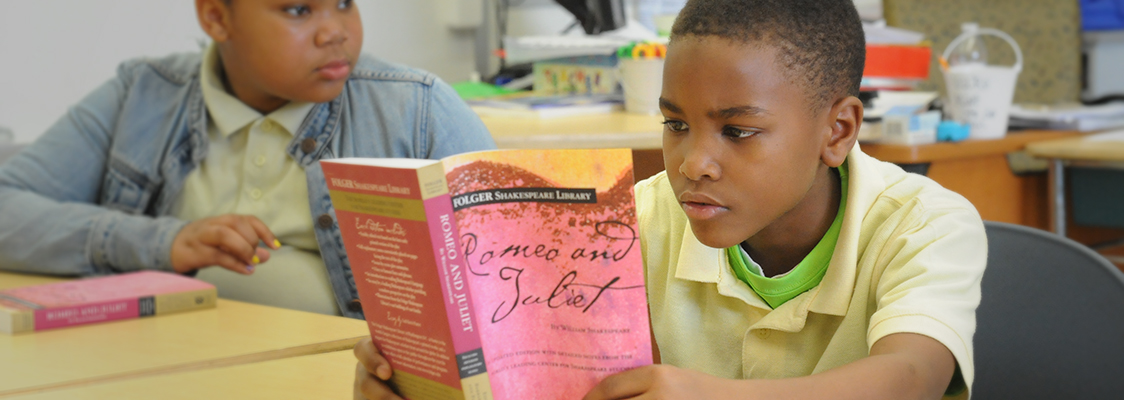 A middle school student reads a Folger Shakespeare Library Edition of Romeo and Juliet.