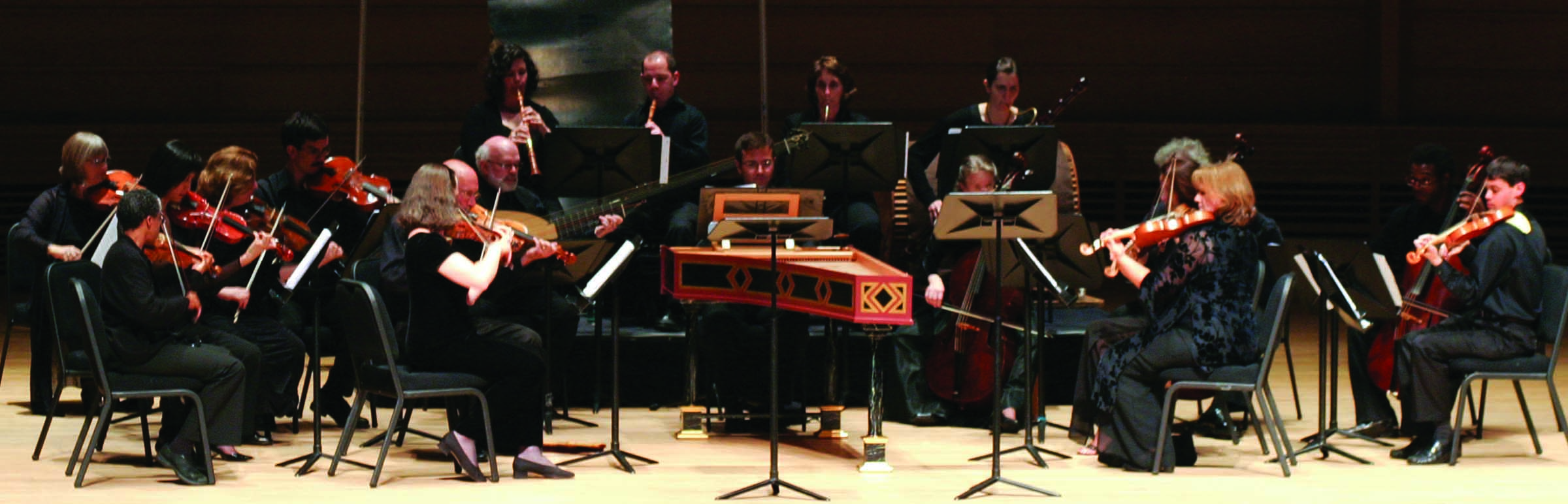 Musicians, singers, and actor bow while onstage in concert hall